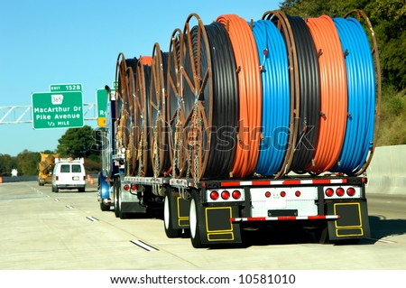 Eighteen wheeler hauls big load of plastic hose.  Each reel contains black, orange and blue hose.  Interstate signs in background. - stock photo