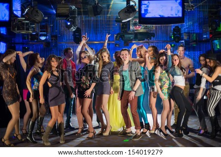 Eighteen young people having fun and dancing at a party - stock photo