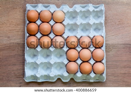 Eightreen Eggs in paper tray on wooden background. - stock photo