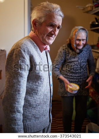 Eighty years old couple indoor in their home - stock photo