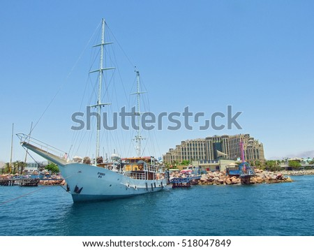 EILAT, ISRAEL - JULY 13, 2007: Big yacht is anchored in front of building of Hilton hotel at the coast of Red Sea in resort town of Eilat.