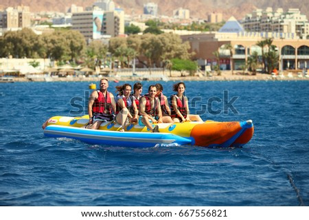 Eilat, Israel - JUNE, 23, 2017: Sea attraction, Group of young enjoying a ride on a banana boat on sunny summer day. Beach water sport