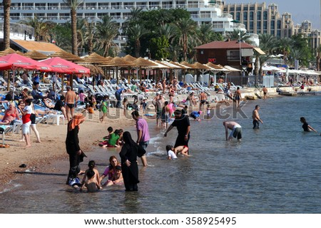 EILAT, ISRAEL -NOVEMBER 18, 2010: Men, women and kids relax on the beach - stock photo