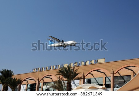 EILAT, ISRAEL - NOVEMBER 18, 2010: Plane flies low over the shopping center to safely land in the airport a minute later - stock photo