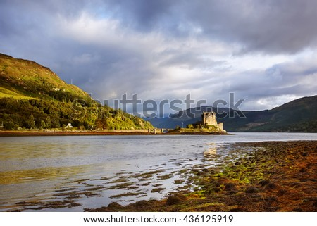 Eilean Donan Castle at sunset. Dramatic landscape with side view of the famous Scottish castle, Scotland, UK - stock photo