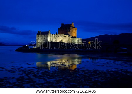 Eilean Donan Castle, Loch Duich, Scotland, at late evening showing lit castle against blue sky - stock photo