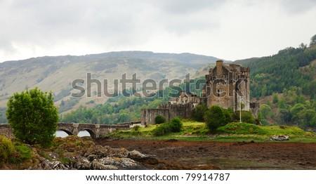 Eilean Donan castle on a cloudy day.    low tide. Scotland - stock photo