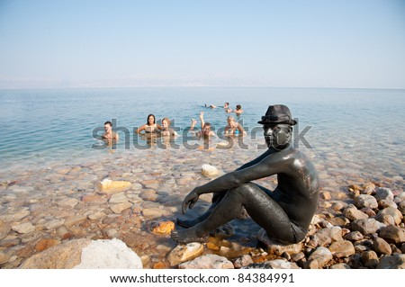 EIN GEDI, ISRAEL - SEPTEMBER 7: Dead Sea beach-goers cover themselves in mud reputed to be good for the skin, and a popular Israeli export, on Sept 7, 2011 in Ein Gedi, Israel - stock photo