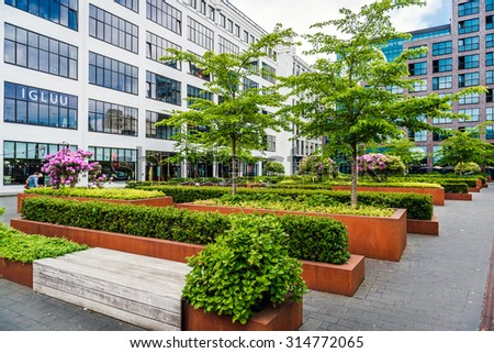 Eindhoven, Netherlands- May 24, 2015: Eindhoven downtown. Lush bushes and benches in the office complex park - stock photo