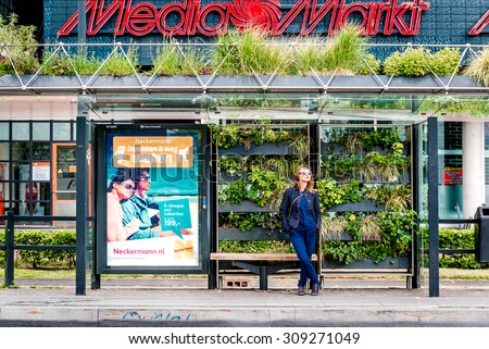 Eindhoven, Netherlands- May 24, 2015: Girl at a Eindhoven green bus stop. The green bus stop was created as part of a competition organized by the Municipality of Eindhoven back in 2009.