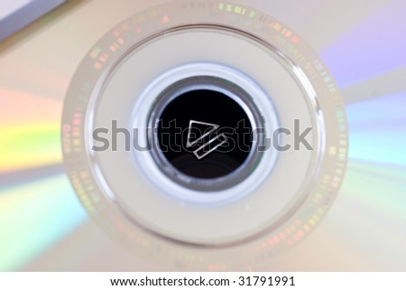 Eject button shown through DVD center hole. Shallow depth of field. - stock photo
