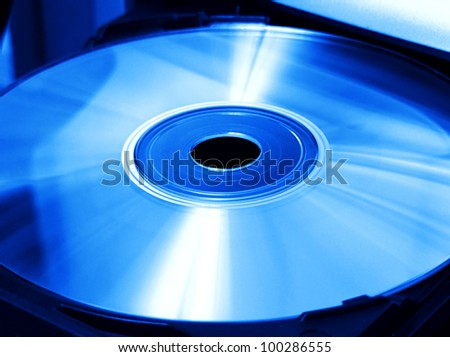 Ejecting or Inserting cd, dvd or blue-ray disk into drive in blue tone. Selective focus. - stock photo
