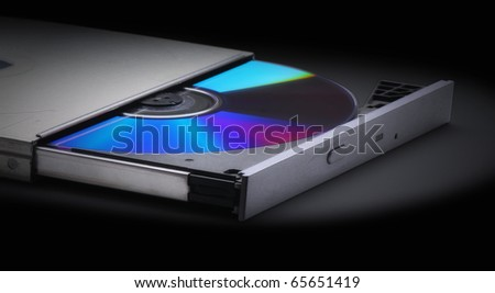 Ejecting or Inserting  cd, dvd or blue-ray disk into drive  without a computer on a black background - stock photo