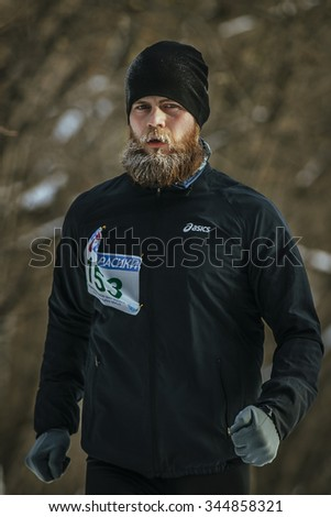 Ekaterinburg, Russia - November 14, 2015: young male athlete with a lush beard running outdoors in cold weather during Urban winter marathon