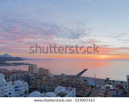 El Campello - 4 October 2015: Beautiful promenade of El Campello, roofs, sun and the sea in the morning at dawn, October 4, 2015, El Campello, Spain