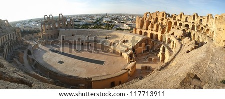 El Djem Amphitheatre panorama. Panorama of central podium and the whole roman amphitheater, with city skyline of El Djam in the background at sunset, Tunisia - stock photo