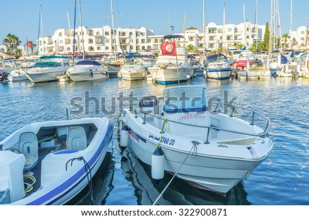 EL KANTAOUI, TUNISIA - AUGUST 29, 2015: The speed motor boats and imposing sailing yachts wait for the trip in Port, on August 29 in El Kantaoui. - stock photo