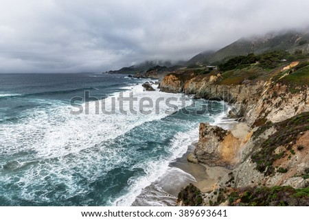 El Nino storm, fog, and gray skies on Highway 1, with aquamarine waters & rock formations, along the rugged Big Sur coastline, near Carmel and Monterey, CA. on the California Central Coast. - stock photo