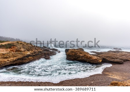 El Nino storm & fog at Point Lobos State Natural Reserve, with aquamarine waters & rock formations, along the rugged Big Sur coastline, near Carmel and Monterey, CA. on the California Central Coast - stock photo