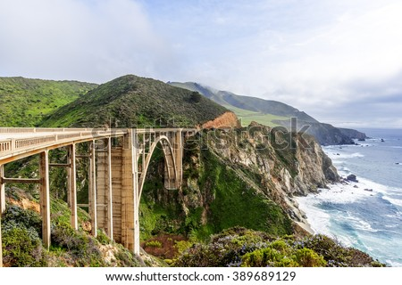 El Nino storm, fog, & gray skies at the Bixby Bridge, with aquamarine waters & rock formations, along the rugged Big Sur coastline, near Carmel and Monterey, CA. on the California Central Coast. - stock photo