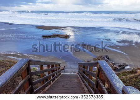 El Nino weather storm floods Central California Coast beach, with powerful wind, rain, waves, & heavy surf. Beach access stairs, washed out, near Cambria, CA. on the Big Sur Coast. - stock photo