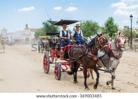 El ROCIO, ANDALUCIA, SPAIN - MAY 22: Carriage rides through the village after the religious procession. Son and father equestrians. 2015 Famous pilgrimage of Spain.  - stock photo