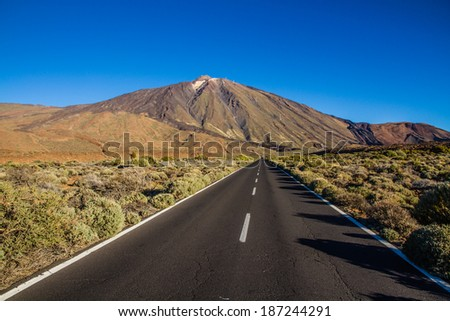 El Teide Volcano Mountain Straight Empty Road and Blue Sky - Tenerife, Canary Islands, Spain - stock photo