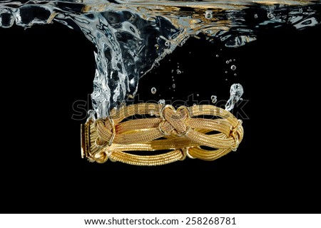 elaborate gold bracelet splashing in water against black - stock photo