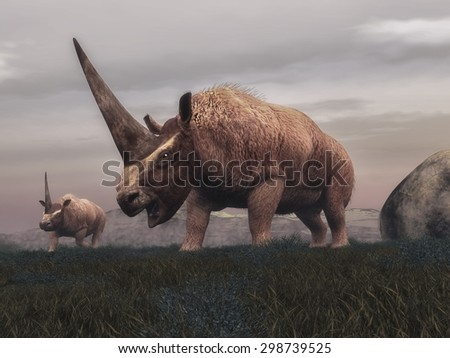 Elasmotherium mammal dinosaurs walking in the steppe grass by cloudy day - 3D render - stock photo
