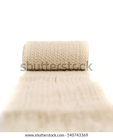 Elastic ACE compression bandage warp unwrapped over white background, shallow depth of field - stock photo