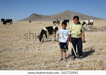 ELAZIG, TURKEY - JULY 3: Young girl and boy shepherds at drought field on July 3, 2008 in Elazig, Turkey. - stock photo