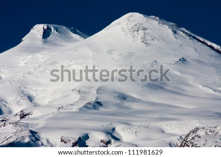 Elbrus - a sleeping volcano cone with two peaks. Western top has height of 5642 m, East - 5621 m. It can be seen on the trail which climbs a mountain climber - stock photo