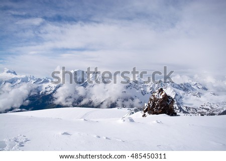 Elbrus - beautiful view down from a height of the Mountain. Peak is very close. Clouds below. Extremely beautiful landscape: neighboring mountains, white snow and clouds, blue sky. Unearthly beauty!