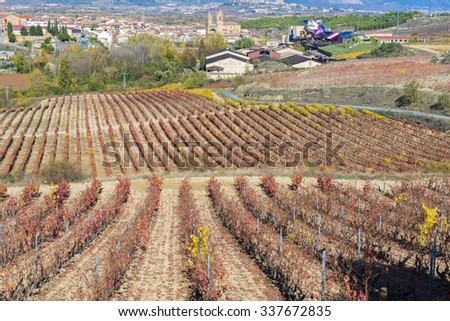 ELCIEGO, SPAIN - NOV 6: Vineyards and town of Elciego with the modern winery of Marques de Riscal on November 6, 2015 in Elciego, Basque Country, Spain. This modern winery was designed by Frank Gehry. - stock photo