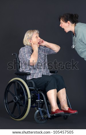 Elder abuse concept with a senior woman in a wheelchair crying and covering her ears as a middle age nurse or other health care worker is yelling at her. - stock photo
