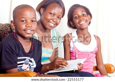 Elder african sister reads to her younger brother and sister - stock photo