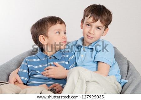 Elder and younger brother sitting on pufe, indoor - stock photo