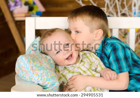 elder and younger brothers children sitting on bench indoors - stock photo
