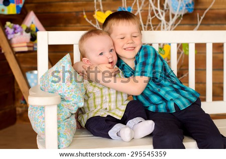 elder and younger brothers kids sitting on bench indoors - stock photo