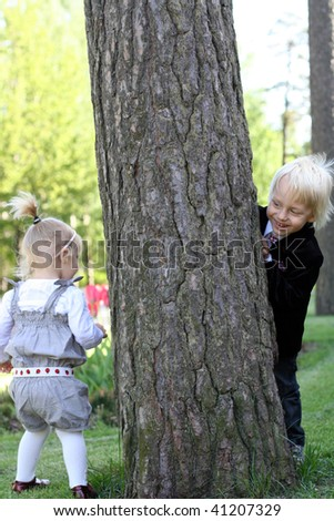 Elder brother is hiding behind a tree from little sister. - stock photo