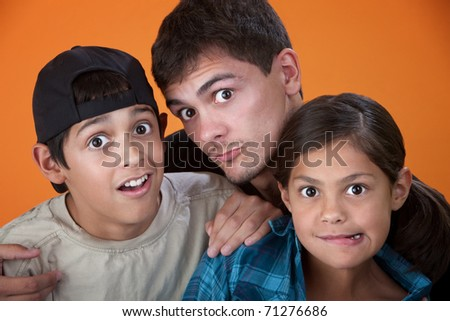 Elder brother with two younger siblings making faces - stock photo
