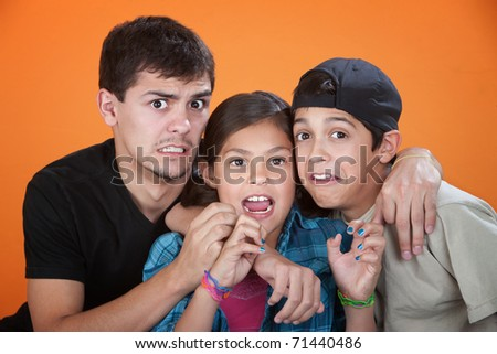 Elder brother with two younger siblings wearing a scared look - stock photo