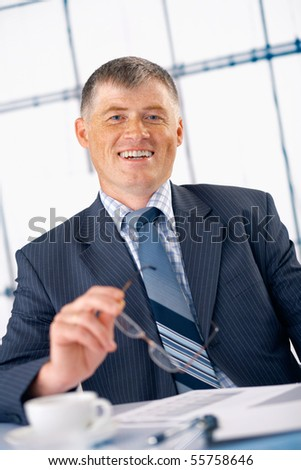Elder business manager smiling and holding glasses in his hand in the office. - stock photo
