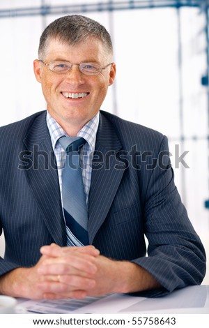 Elder businessman smiling and sitting at his office with his fingers crossed.
