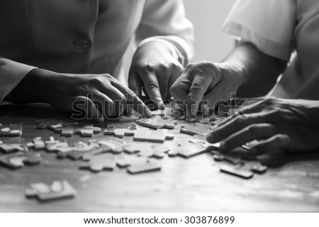 Elder care nurse playing jigsaw puzzle with senior man in nursing home. black and white - stock photo