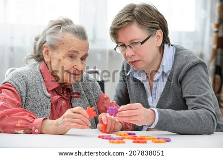 Elder care nurse playing jigsaw puzzle with senior woman in nursing home - stock photo