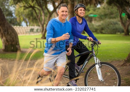 Elder couple exercising in the park - stock photo