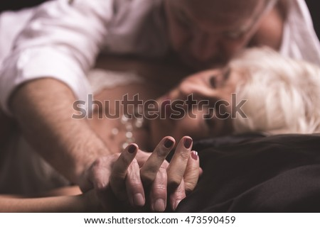 Elder couple lying together on a bed in an erotic love hug with intertwined fingers