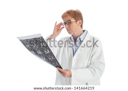 elder female doctor in a white lab coat viewing a magnetic resonance tomography print of a skull - stock photo