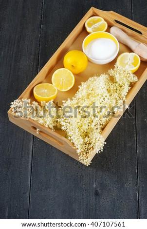 elder flower juice ingredients on wooden tray, black wood table background - stock photo